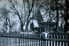 Otoczenie kościoła: naprzeciw głównego wejścia dzwonnica oraz parkan drewniany okalający teren przykościelny i teren cmentarza.